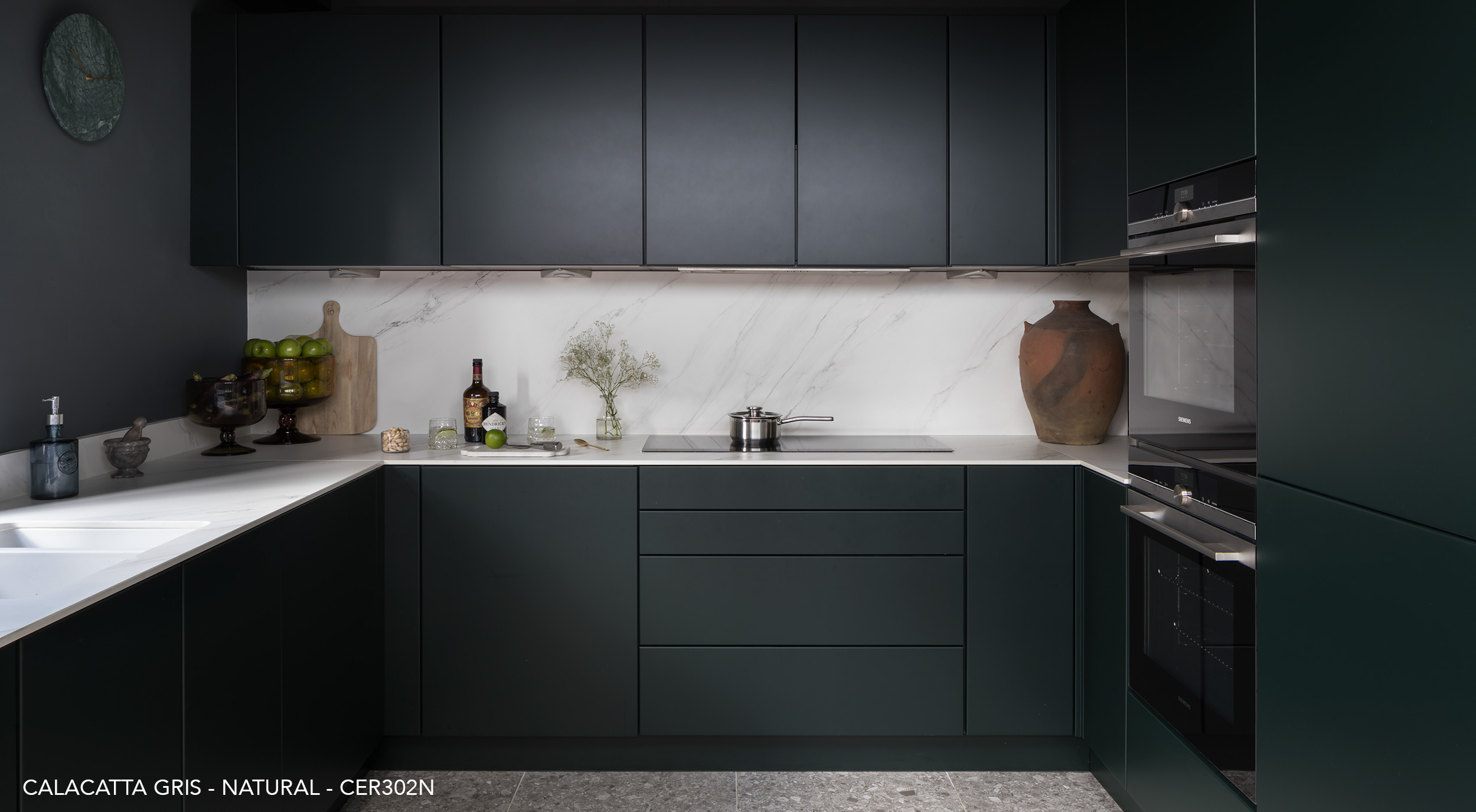 U-shaped kitchen with Ceralsio Calacatta Gris worktop and dark green cupboards