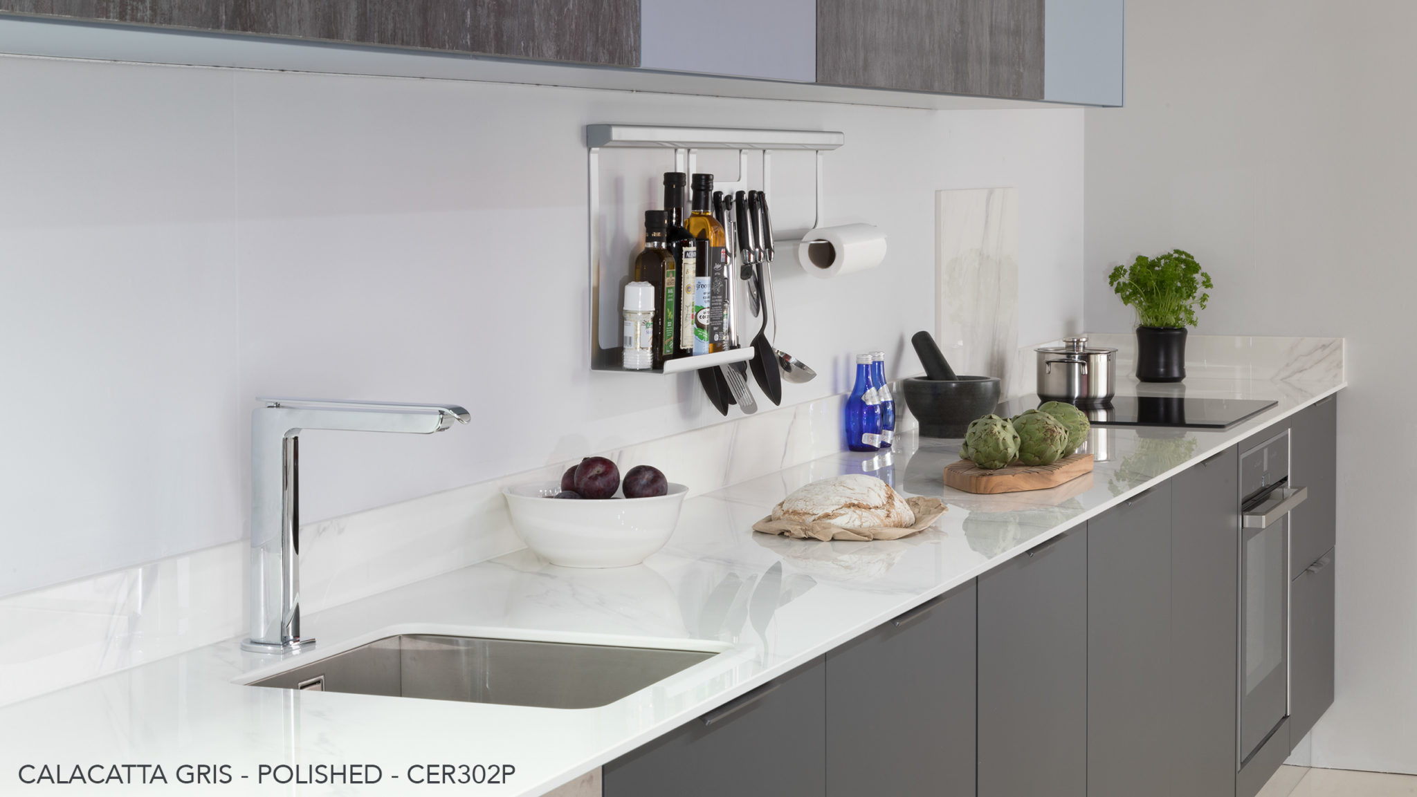 Ceralsio Calacatta Gris white/grey veined worktop with stainless steel kitchen accessories.